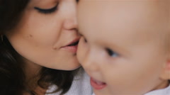 Young Happy Mother Holding her Newborn Child and kissing. Family at home Stock Footage
