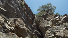 A rock climbing route with rocks and trees in the mountains. Stock Footage