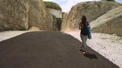 Beautiful woman walking with yoga mat in canyon Stock Footage