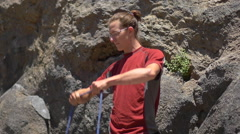 A young man preparing his rope before going rock climbing. Arkistovideo
