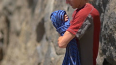 A young man preparing his rope before going rock climbing. Stock Footage