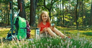 Hiker girl 8-9 years pours tea from a thermos sitting on the grass in forest Stock Footage