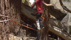 A man balancing on a slackline while reading a book. Stock Footage