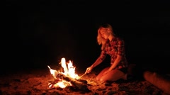 Girl keeping camp fire at night Stock Footage
