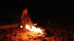 A Girl keeping camp fire at night Stock Footage