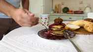 Bearded man eats with appetite Pancake in the kitchen Stock Footage