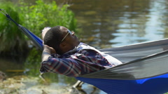 A man resting in a hammock near a mountain lake. Stock Footage