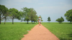 A young woman walking with a longboard skateboard. Stock Footage