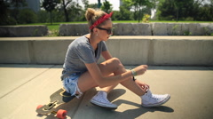 A young woman tying her shoes while sitting on her longboard skateboard. Stock Footage