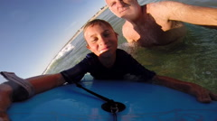 A father helps his son to go body boarding in the waves at the beach. Stock Footage