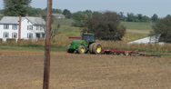 Green Tractor Plowing Farm Field Country House in Background, 4K Stock Footage