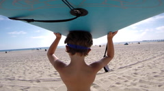 A boy holding his board to go body boarding at the beach. Stock Footage