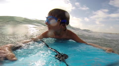 A boy body boarding in the waves while where goggles at the beach. Stock Footage