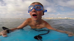 A boy wearing goggles and sinking under waves while body boarding at the beach. Stock Footage