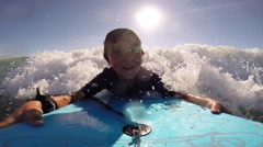 A boy body boarding in the waves at the beach. Stock Footage