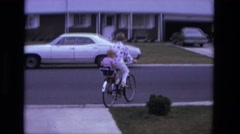 1975: leaving driveway mom toddler bike ride in tandem safety seat  Stock Footage