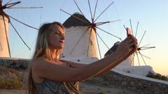 Blonde model takes selfie in front of windmills mykonos greece slow motion Stock Footage