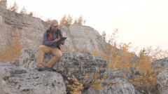 Young, Lost Man With Using Tablet Looking For Direction On The mountain.  Cau Stock Footage