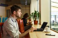 Young man with laptop in city cafe, freelancer Stock Photos