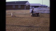 1975: woman on lawn mower pulling child in wagon behind her CALIFORNIA Stock Footage