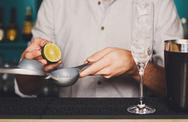 Barman's hands making cocktail with lime Stock Photos