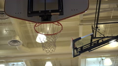 A basketball going through the hoop in an indoor gym. Stock Footage