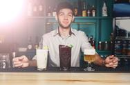 Young Barman offers cocktails in night club bar Stock Photos