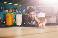 Young Barman offers non-alcoholic cocktails in night club bar Stock Photos