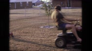 1975: dad riding lawn mower tractor pulling son in small red wagon CALIFORNIA Stock Footage
