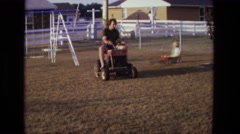 1975: aa father pulling his son's mini car with pruner in the backyard Stock Footage