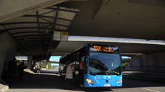 Passengers board the bus and depart from the bus stop. Stock Footage