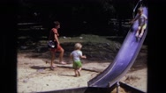 1975: child running while his mother follows behind on sunny day at the park. Stock Footage