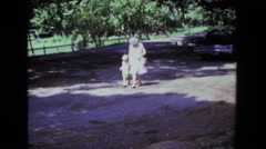 1975: woman in her seventies strolling with young child down an unpaved road in Stock Footage