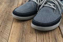 Blue Sneakers with wooden background Stock Photos