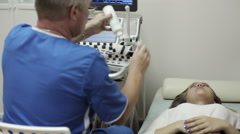 Male doctor talking with young woman patient in ultrasound diagnostic room. Stock Footage