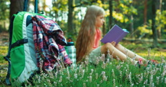Hiker girl child 8-9 years reading book in the forest and smiling at camera Stock Footage
