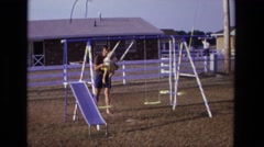 1975: dad stopping child on swing set to toddler can play CALIFORNIA Stock Footage