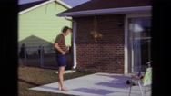 1975: man summertime backyard porch area lighting up cigarette CALIFORNIA Stock Footage