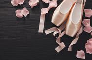 Pink ballet pointe shoes on black wood background Stock Photos