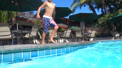A boy doing a cannonball and jumping into a pool at a hotel resort. Stock Footage