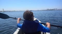 A boy paddling in a kayak in Mission Bay, San Diego. Stock Footage
