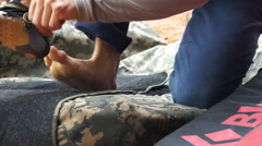A man puts on his shoes for bouldering rock climbing. Stock Footage
