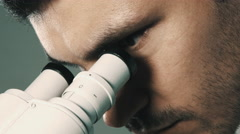 Young scientist looking through the microscope Stock Footage