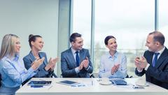 Business team with laptop clapping hands Kuvituskuvat