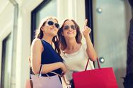 Happy women with shopping bags in city Stock Photos