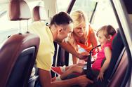 Happy parents fastening child with car seat belt Stock Photos
