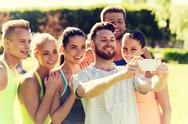 Happy friends taking selfie with smartphone Stock Photos