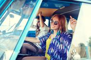 Smiling young hippie women driving minivan car Stock Photos
