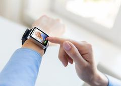 Close up of hands with incoming call on smartwatch Stock Photos