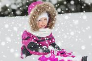 Happy kid in winter clothes playing with snow Stock Photos